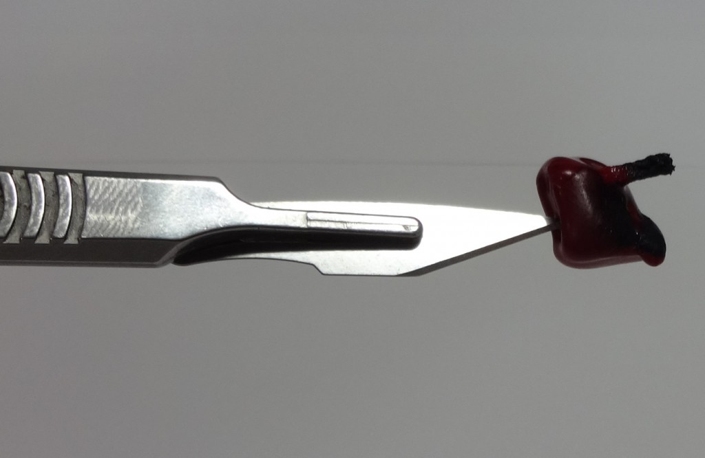 Sealing wax on the tip of a scalpel blade